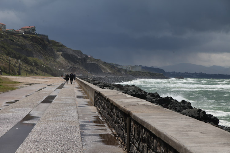 Couple strolls the sea as the clouds briefly part in Biarritz, France.
