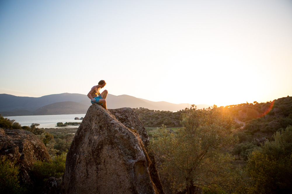 Climber Jovi enjoys the last light at the top of a boulder in Bafa Lake Turkey.